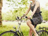 Une jeune femme pédalant un vélo dans un parc de Londres, en Angleterre.