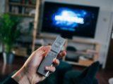 Une personne tenant une télécommande devant la télé.