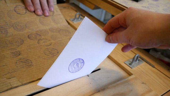 Une personne introduit son vote dans une urne.