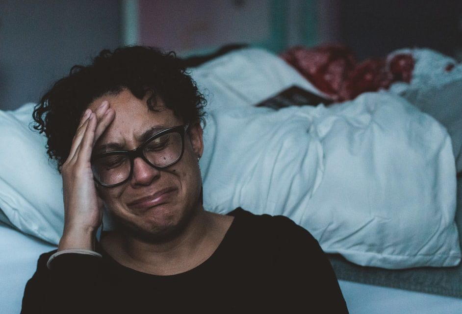 Une femme pleurant dans une chambre (Image : Unplash).