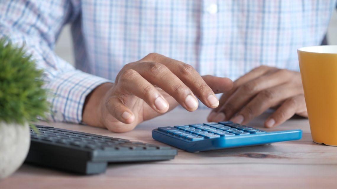 Un homme manipulant une calculatrice